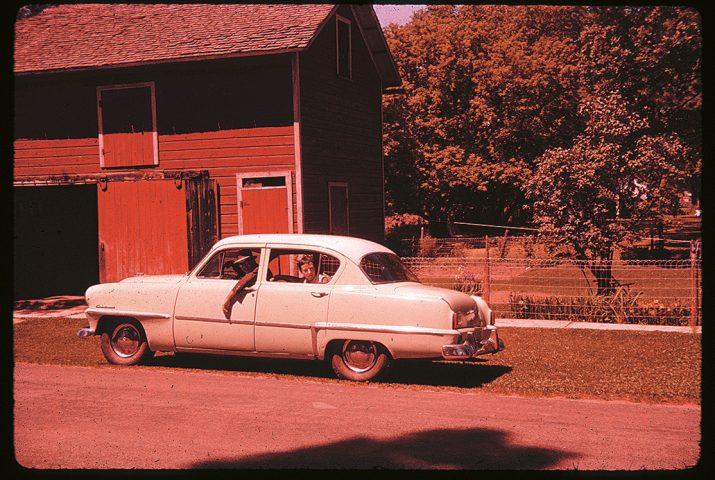 Auto mit Insassen vor einem Holzhaus