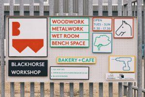 Schilder auf einem Metallzaun, welche über die Öffnungszeiten und den Blackhorse Workshop informieren