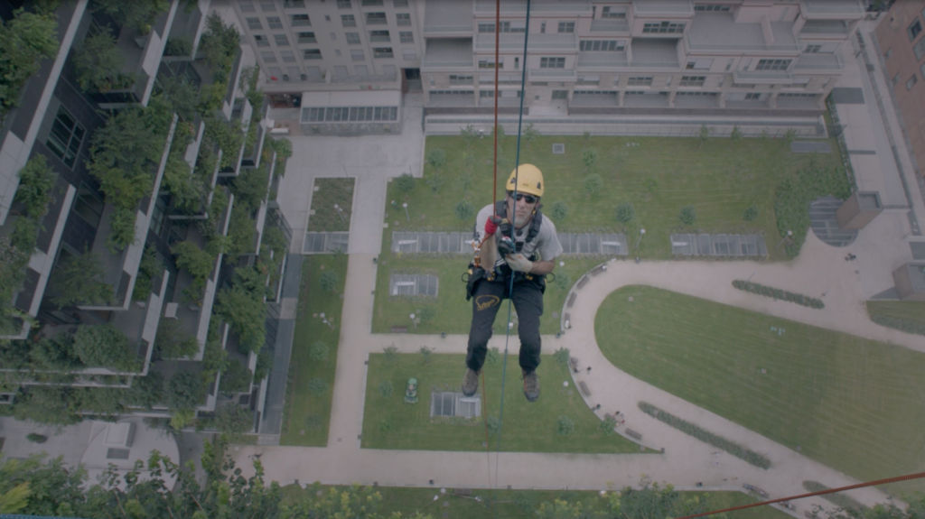 Person secured to a cable, hanging beside a building