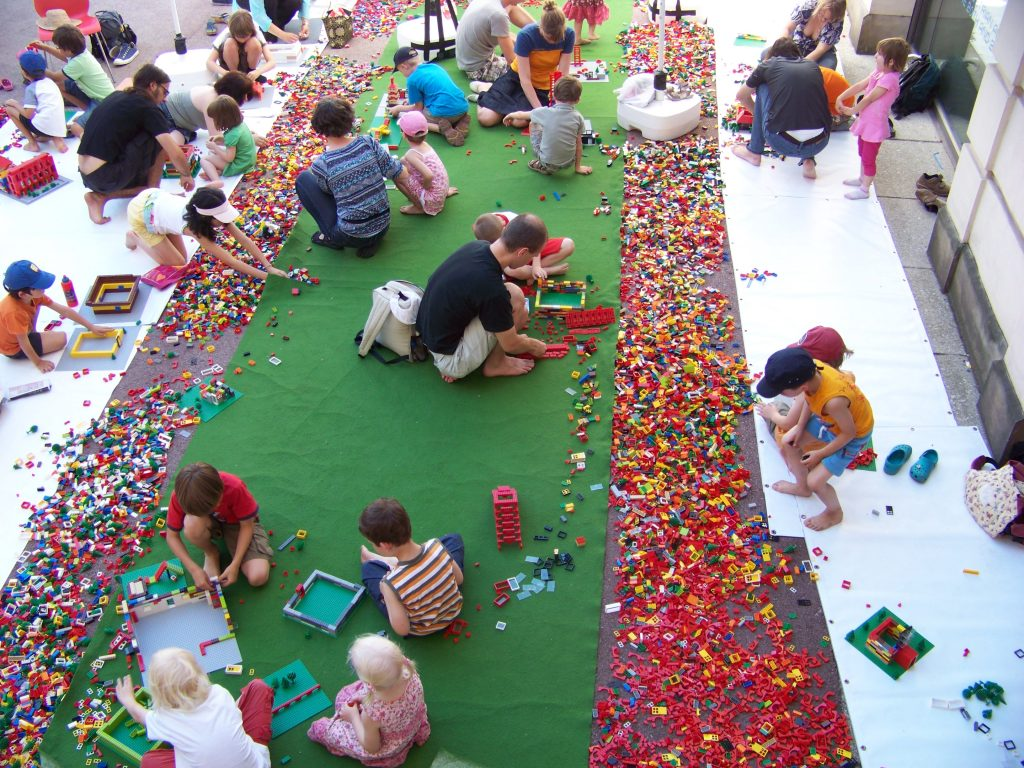 Viele Menschen bauen mit sehr vielen Legosteinen Gebäude