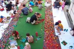 Lots of people erecting buildings using a huge amount of Lego bricks