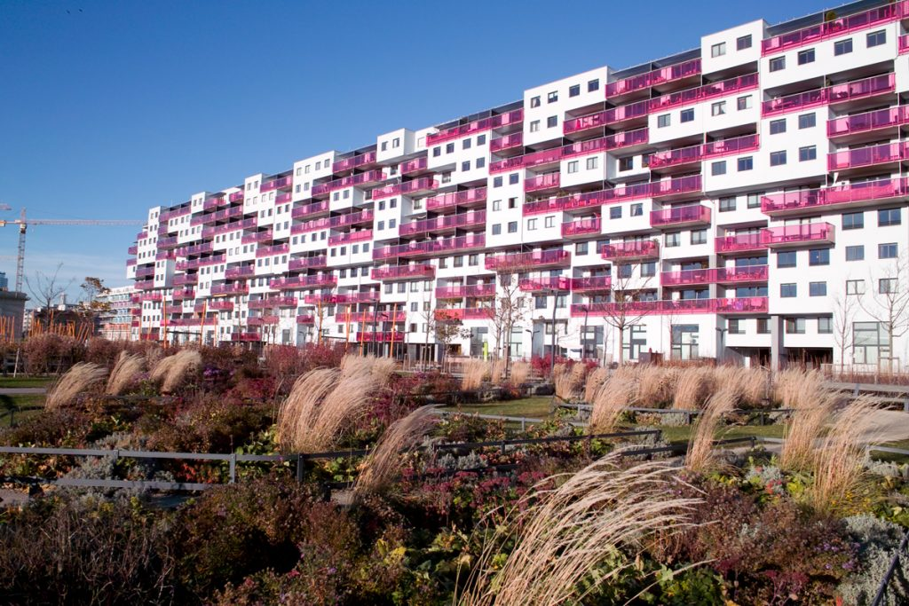 Ein langgestreckter Wohnbau mit pinkfarbenen Balkonen