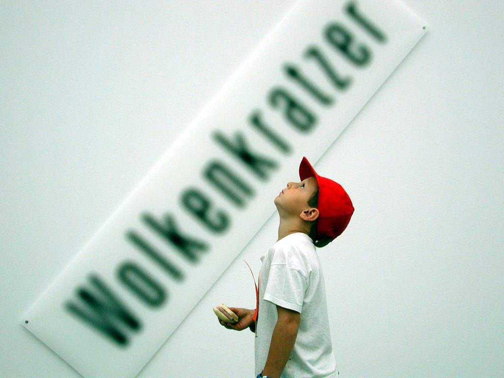"A young boy looks upwards, the German word for ""skyscraper"" is written on a sign beside him."