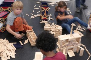 Three children building a model with Kapla blocks