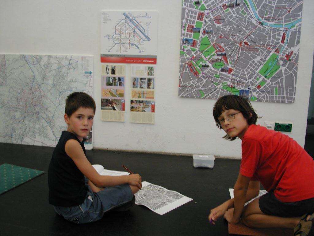 At a workshop two children look at different plans of Vienna.