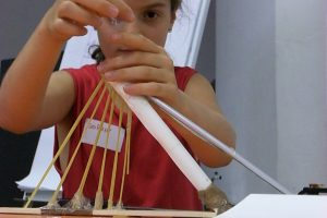 A child working on the model of a bridge.