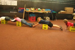 Children try out the forces in a bridge with their own bodies.