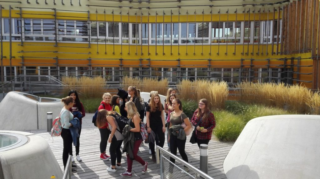 Schüler*innengruppe vor einem gelb-orange gestreiften Gebäude