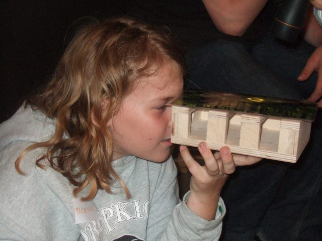 A child looking through a wood model that simulates a lighting situation