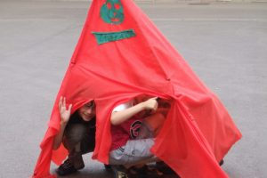 Children in a red tent they have built themselves