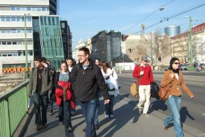 Group of school students crossing the Danube Canal, an office tower can be seen in the background.