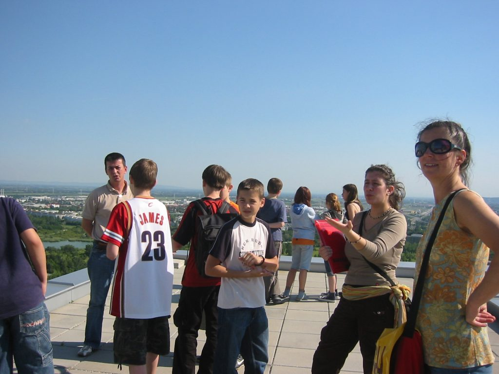 Group of school students on a roof, admiring the view of Vienna