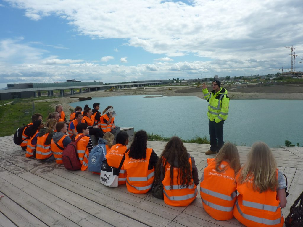 Group of school students wearing orange jackets sitting beside a lake