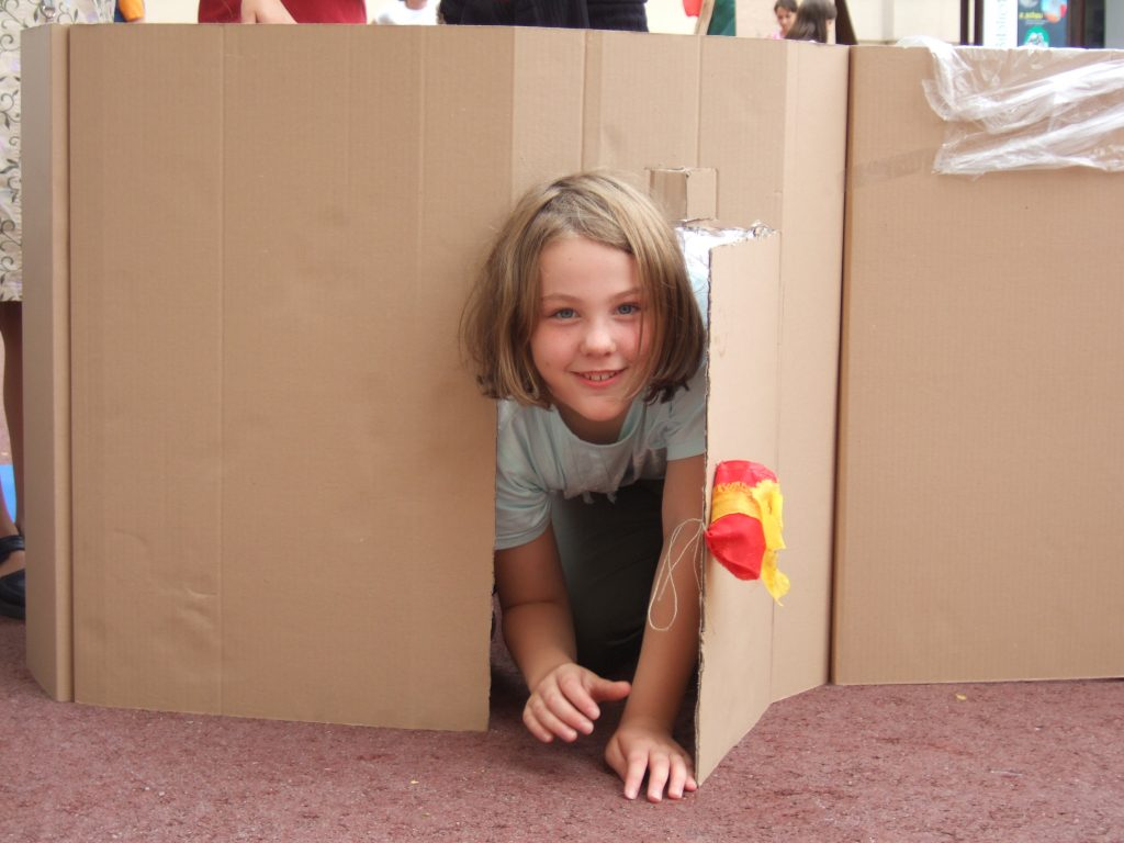 A child clambers out of a cardboard house she built himself