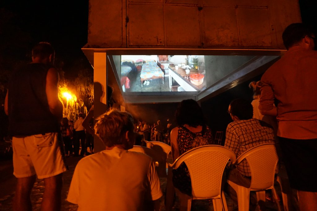 People sitting watching a film at night