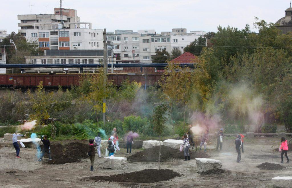 Schüler*innen verteilen Samenkugeln, die Farbpigmente enthalten, in einem Park