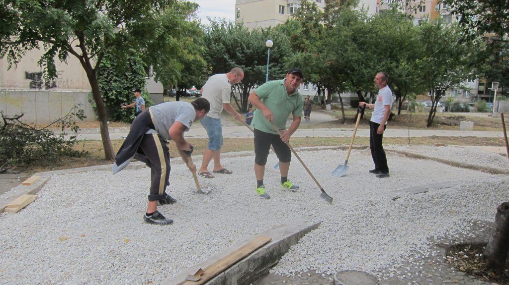 Männer verteilen mit Schaufeln und Rechen Steine in einem Beet