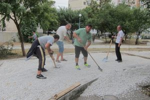 Men using shovels and rakes to spread stones in a bed