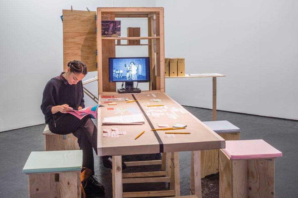 Lesende Frau an einem Tisch