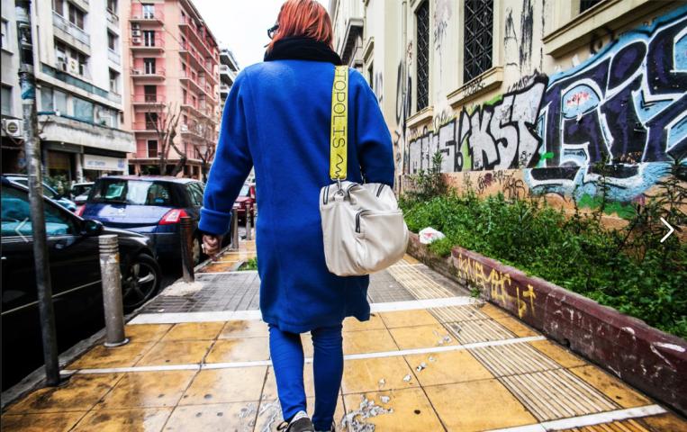 Ein Mensch, dessen Rückenansicht man sieht, geht auf einer Straße in einer Stadt