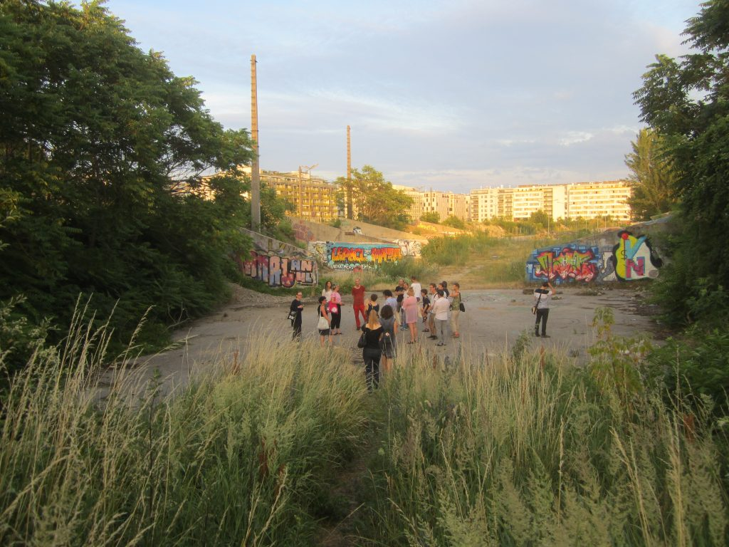 People walking through the overgrown landscape at Nordbahnhof