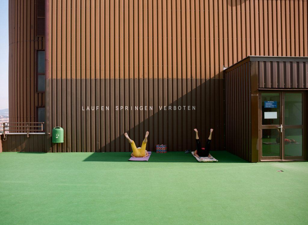 2 Menschen turnen auf Matten am Boden vor dem Eingang eines Hauses, auf dem geschrieben steht: Laufen, Springen, verboten