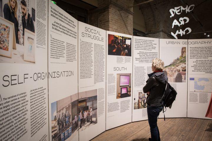 Eine Person vor Ausstellungstafeln stehend