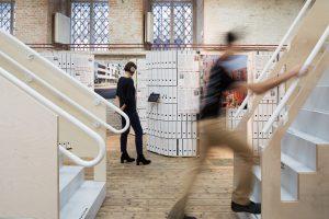 Mann geht Treppe hinauf und eine Frau steht im Hintergrund bei Ordnerwand