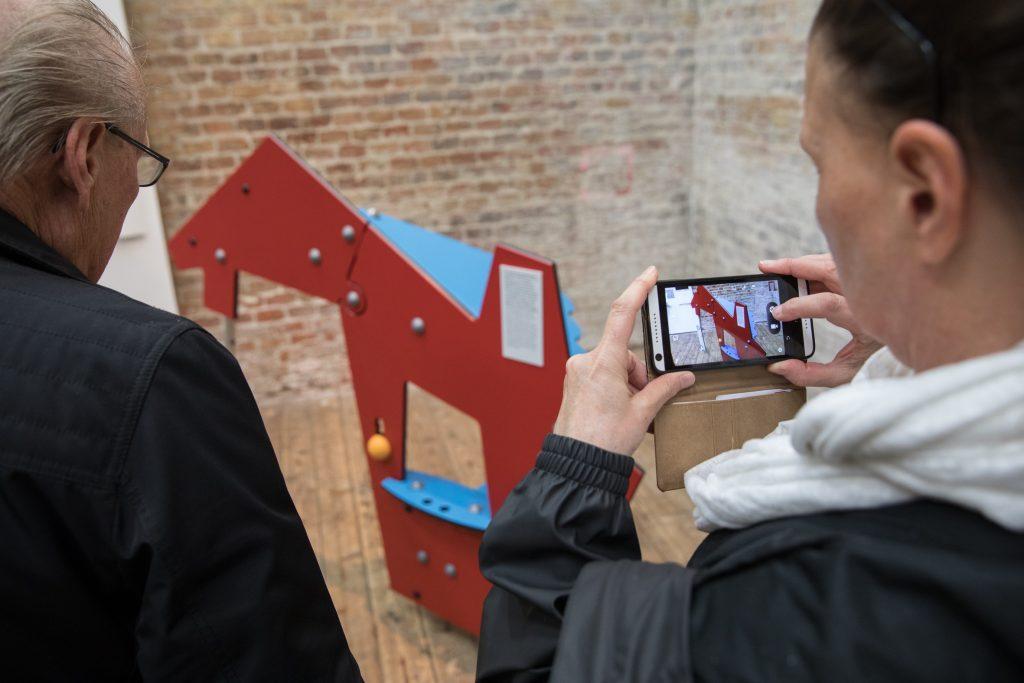 Junger Mann fotografiert mit dem Smartphone ein Spielhaus