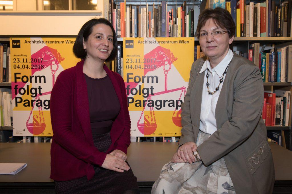 Zwei kluge Frauen sitzen vor einem Plakat