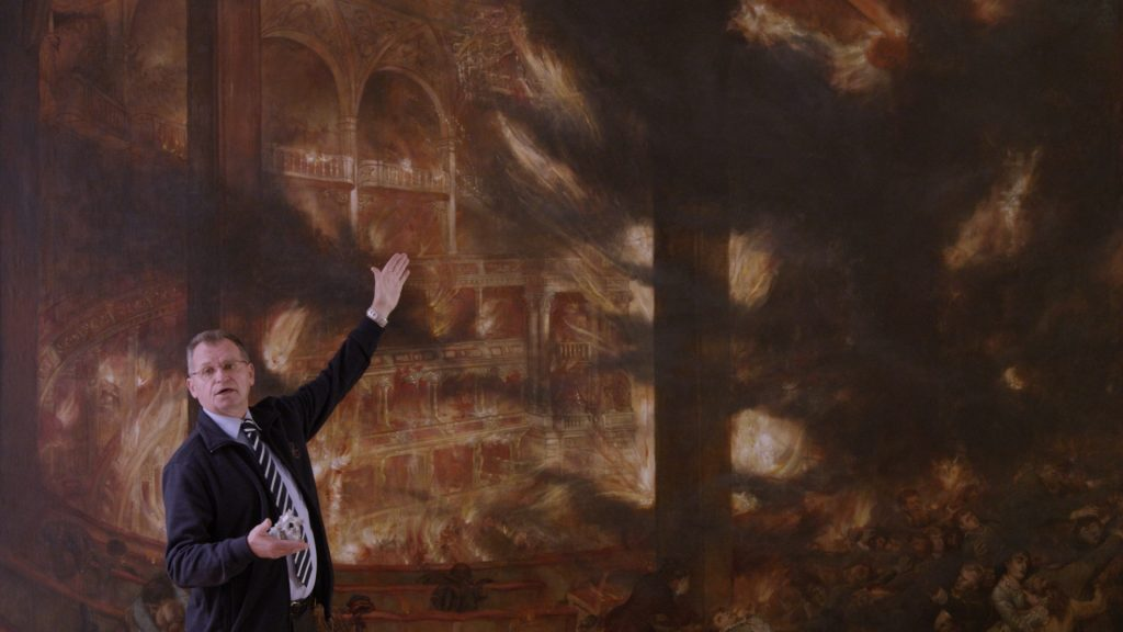 A man points at a painting of the burning Ringtheater in 1881