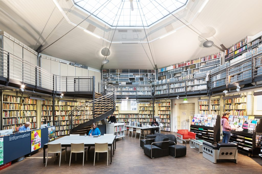 Raum mit vielen Büchern , mehrere Tische, Frau mit blauer Jacke