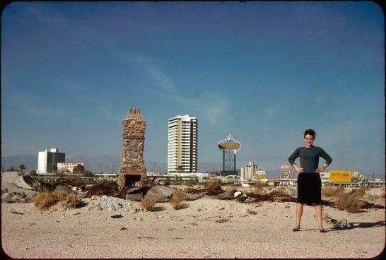 Eine Frau steht am Strand, im Hintergrund Hochhäuser