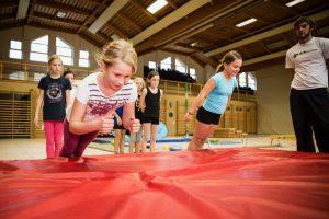 Fotocollage, die Kinder beim Fallen auf Matten zeigt