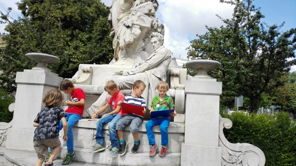 Kinder sitzen auf einem Monument