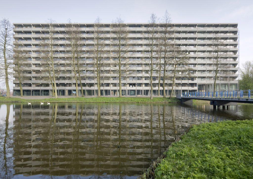 Rechteckiger Wohnblock aus Beton mit Bäumen und See im Vordergrund
