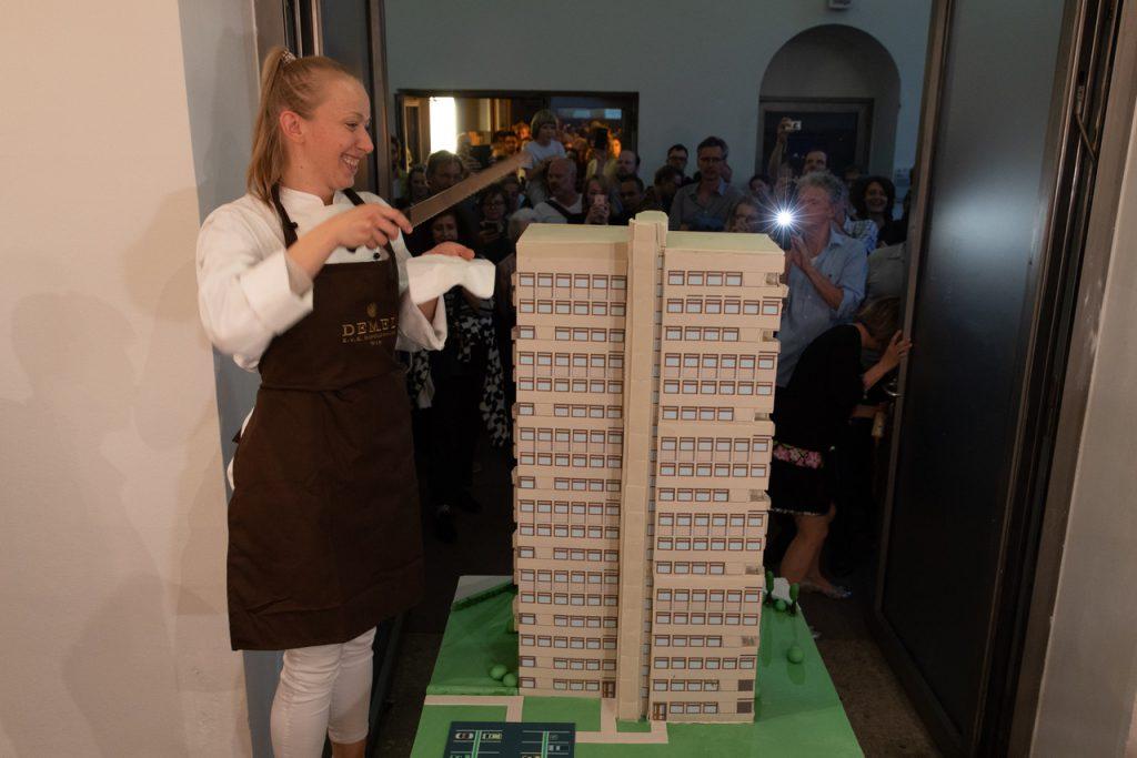 eine Tortenbäckerin mit großem Messer und einer Schürze schneidet einen Kuchen in vorm eines Hochhauses an
