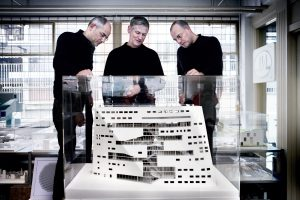 Three man standing around an architectural model