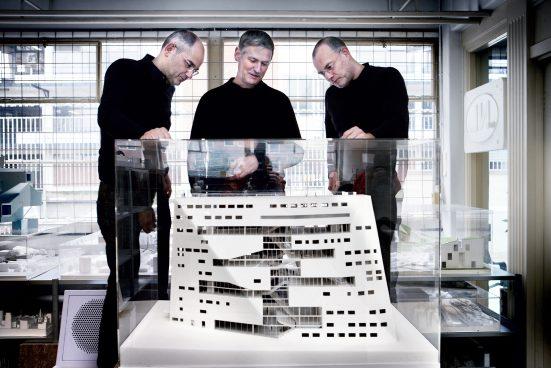 Three man standing around an architectural model