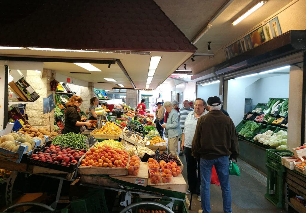 Obst- und Gemüsestand mit Menschen davor in einem Raum.