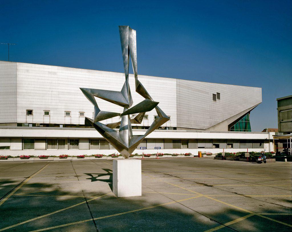 Außenansicht eines mehrstöckigen Flachbaus mit grauer Fassade, im Vordergrund ein Platz mit einer modernen Skulptur in der Mitte