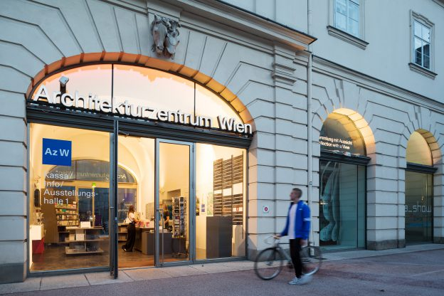 Mann mit blauem Annorak schiebt sein fahrrad am erleuchteten Eingangsbereich des Az W vorbei
