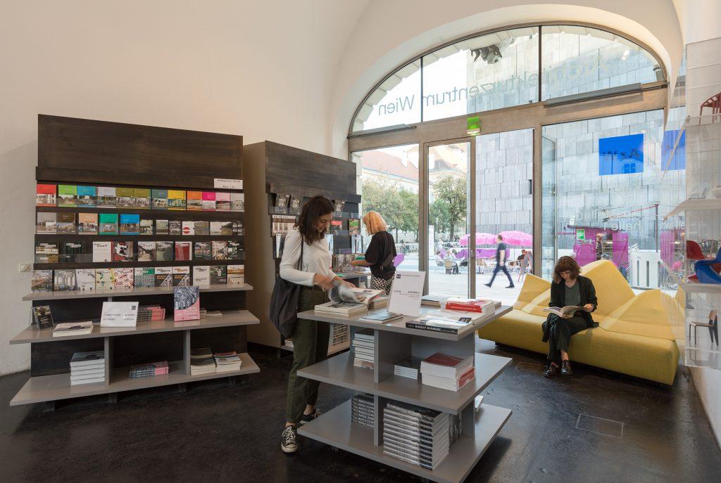 Innenansicht einen Raumes mit Bücherregal , Büchertisch und Sofa und drei lesenden Frauen