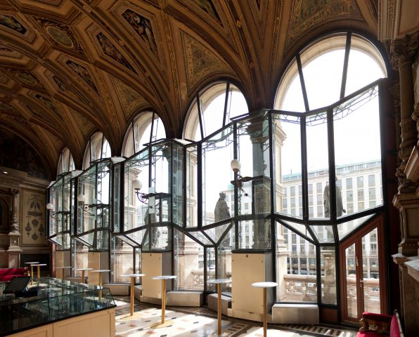 view out of large semicircular windows with sculptures in front of the windows