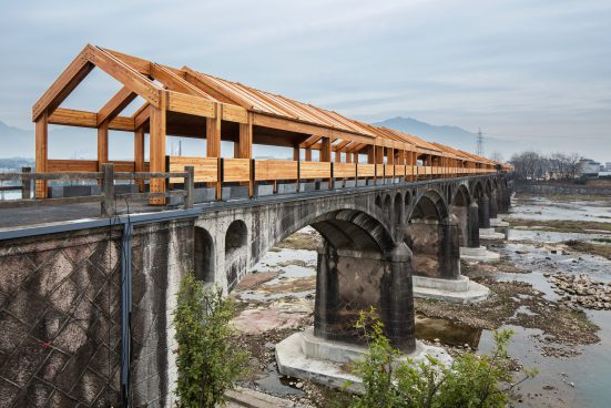 A bridge over a river with old stone viaduct arches and a new wooden structure on top