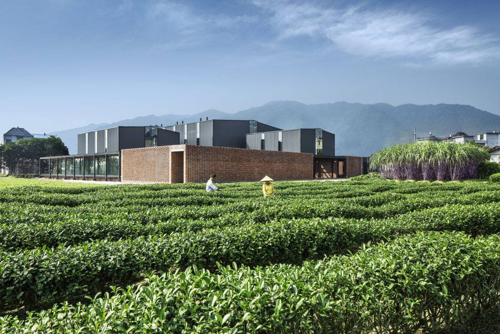 Cube-shaped, brown flat building with three elevated grey elements; in the foreground a tea plantation with 2 workers