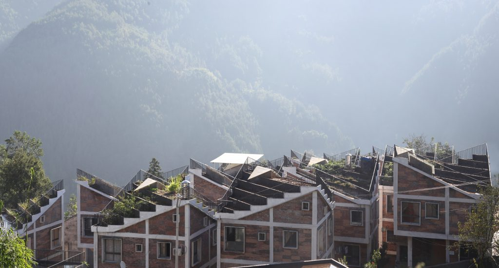 Single-storey terraced houses with partly green terraces on the roof; wooded hills in the background