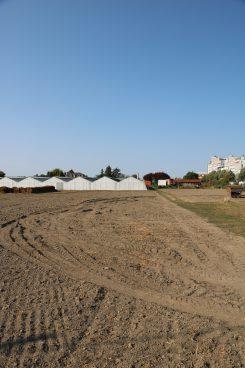 weiße flache Lagerhallen mit einem Acker im Vordergrund