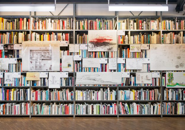 Shelves filled with books to which paper sketches are attached
