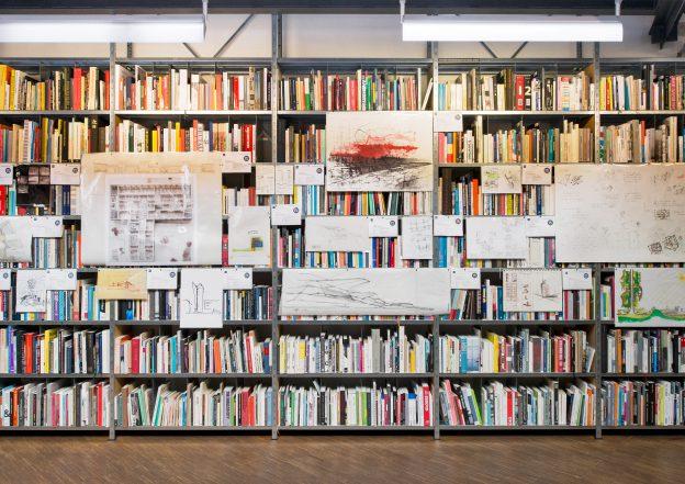 Mit Büchern befüllte Regale an denen Papierskizzen angebracht sind